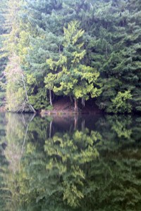 The lake is so calm that the reflections are mirrorlike.