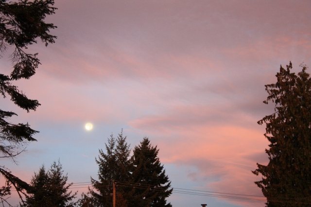 The rising sun paints the clouds around the descending moon.