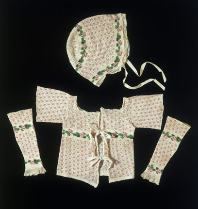 Set of baby's clothing Great Britain Between 1800 and 1849 Hand knitted wool Length of neck to hem of jacket 21 cm; length of arms of jacket outstretched 26 cm; length of sleeve 18 cm; width of sleve at widest point 7 cm, crown to edge of hat 17.5 cm, width of hat at widest point 21.5 cm 380 to C-1907 These pretty baby clothes make up a matching set consisting of a jacket, pair of sleeves and a cap. They are made of stocking stitch decorated with an openwork design, clusters of pink beads and rose motifs made out of pink and green glass beads. The beads would have to be strung on the yarn in the exact reverse order of the pattern before the knitting began. The jacket and cap have tapes attached to secure the clothes to the baby. Separate sleeves were a common part of baby's outfits. The 1838 Workwoman's Guide illustrates and describes how to make a 'Knit Armlet...Little children, in severe weather, wear them over their little naked arms to prevent them from chapping'. .