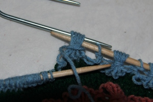 Slip tip of right hand needle through the sts on the cable hook.